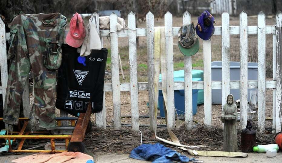 Recovered and camping items hang on a picket fence at the Sauders' home in Sabine Pass, Friday. Hurr