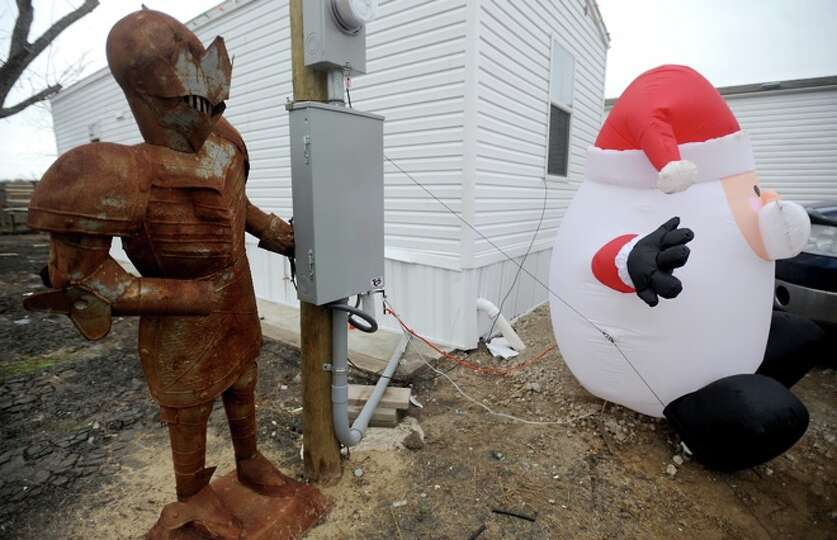 A rusty knights armour and an inflatible Santa decorate the outside of a couple of FEMA trailers in