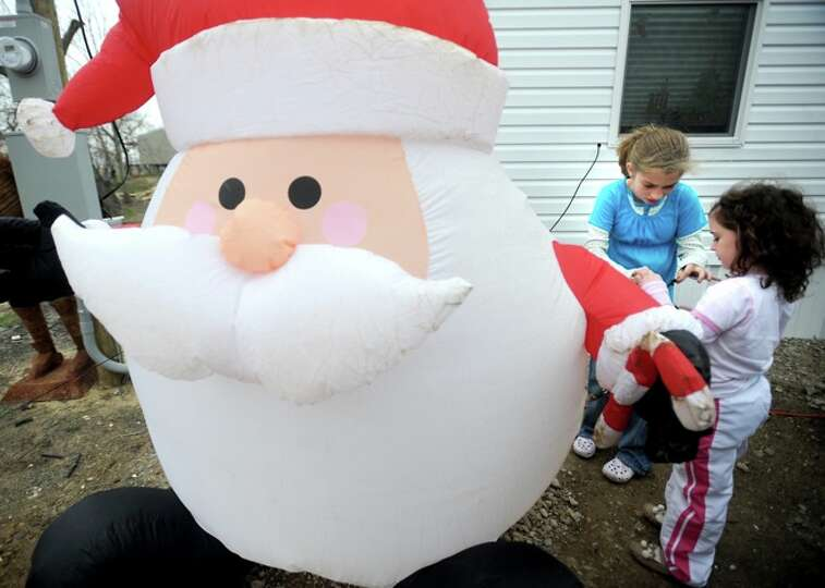 Olivia Saunders and Chrislyn LaFauci play near an inflatible Santa in front of a FEMA trailer in Sab