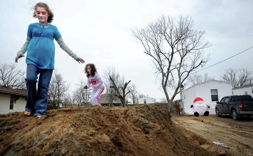 Olivia Saunders and Chrislyn LaFauci play on mounds of dirt near FEMA trailers in Sabine Pass, Frida