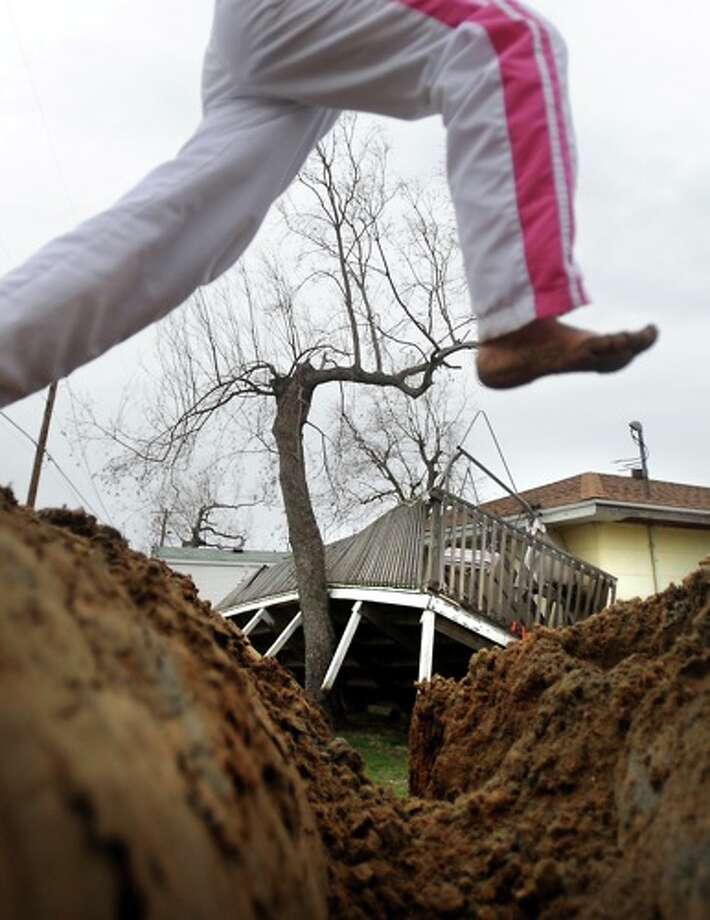 Chrislyn LaFauci plays on mounds of dirt left behind in the aftermath of Hurricane Ike flooding as a home damaged by the storm sits in the background in Sabine Pass, Friday. Photo: TAMMY McKINLEY