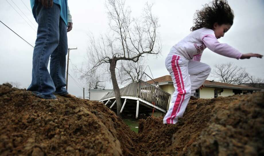 Chrislyn LaFauci and Olivia Saunders play on mounds of dirt left behind in the aftermath of Hurricane Ike flooding as a home damaged by the storm sits in the background in Sabine Pass, Friday. Photo: TAMMY McKINLEY