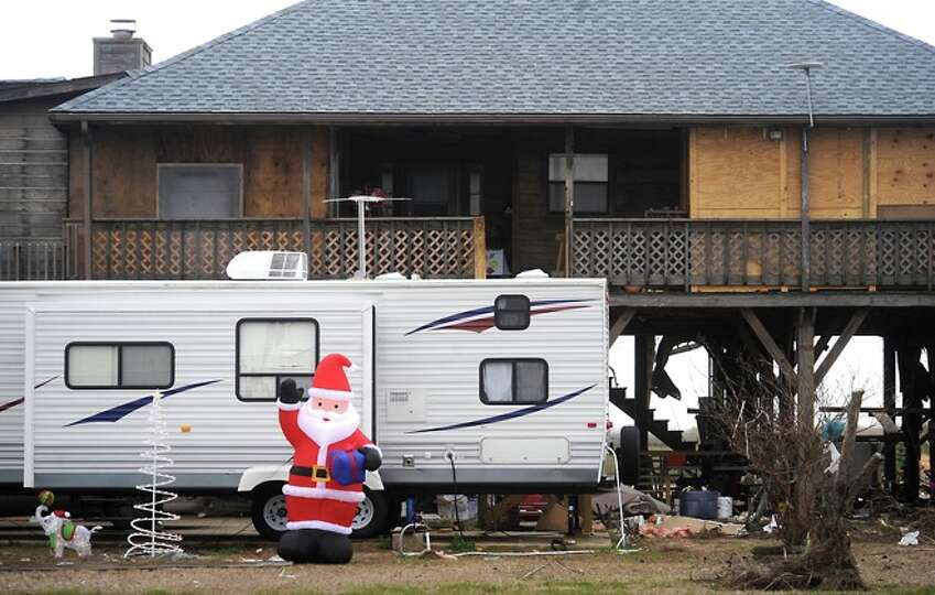 An inflatible Santa sits in front of a camper Bob Sexton is living in while rebuilding his home in S