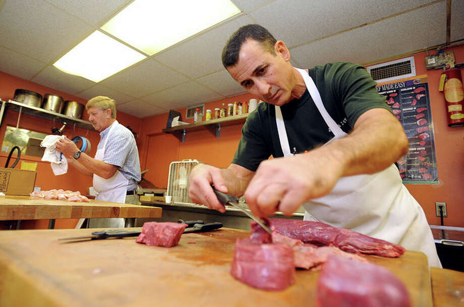 From left, Robert Boehme and Louis Blanda trim meat at Jack-Pack-It on Tuesday. Although suffering home damage, Blanda re-opened the store's doors shortly after Hurricane Ike hit offering food supplies to the public. Guiseppe Barranco/The Enterprise Photo: EMILY GUEVARA