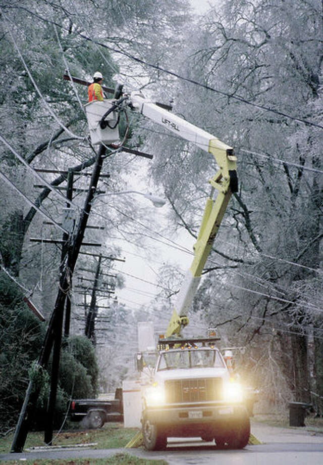 Entergy linemen work to retsore power after the January, 1997 ice storm. Scott Eslinger/ Photo: THE ENTERPRISE