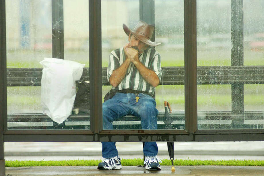 Bus commuter George Holliday Jr., of Beaumont, plays his harmonica and keeps dry in the comfort of a bus stop shelter at Parkdale Mall on Thursday, July 24, 2008.  Valentino Mauricio/The Enterprise