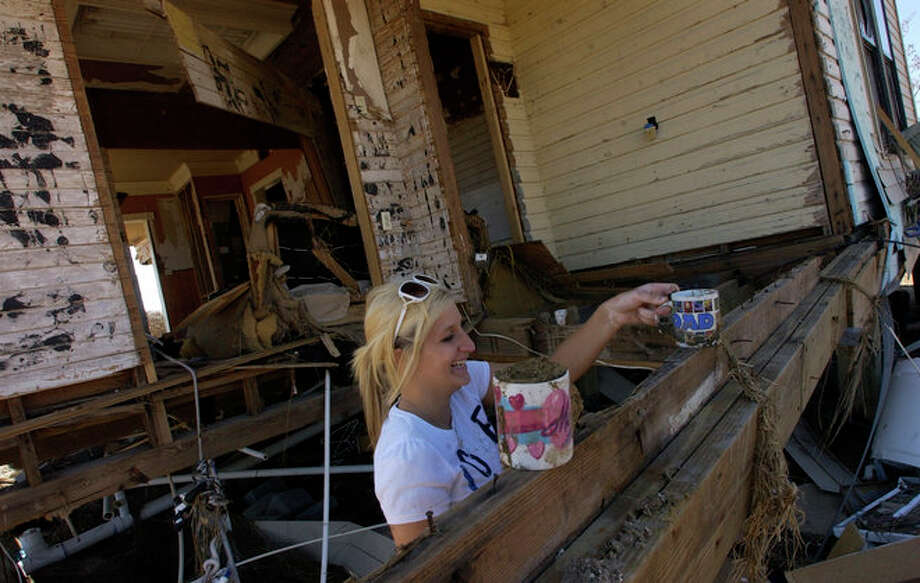 """Sabine Pass High School Senior Rachael Olson, finds her mother's """"MOM"""" and """"DAD"""" mugs in the debris that used to be part of the kitchen.   The  home in Sabine Pass was hit hard by Hurricane Ike's storm surge, but Becky's bedroom, on the top most level, was still intact and most of her personal items were not water damaged.    Dave Ryan/The Enterprise Photo: Seames O'Grady"""