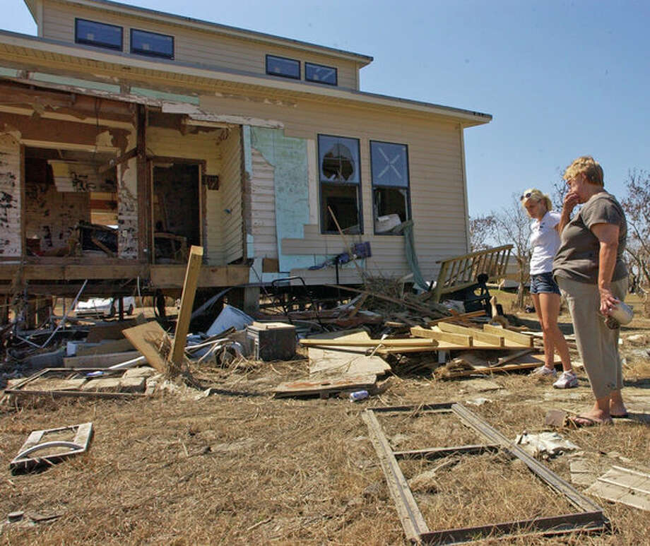 Sabine Pass High School Senior Rachael Olson, left, and her mother Jennifer Olson, right, try to decide where to search for family items Wednesday afternoon.   The  home in Sabine Pass was hit hard by Hurricane Ike's storm surge, but Becky's bedroom, on the top most level, was still intact and most of her personal items were not water damaged.    Dave Ryan/The Enterprise Photo: Seames O'Grady