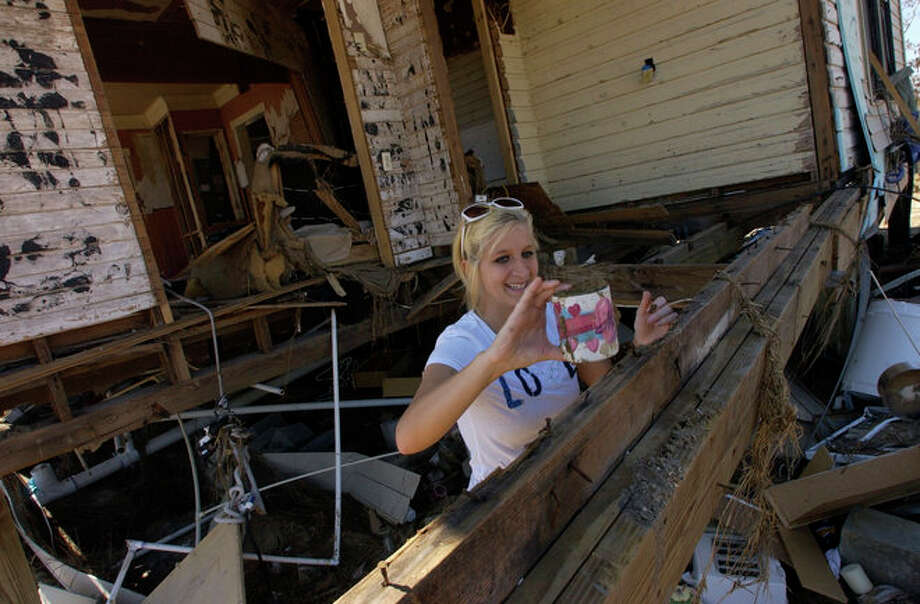 """Sabine Pass High School Senior Rachael Olson, finds one of her mothers """"MOM"""" mugs in the debris that used to be part of the kitchen.   The  home in Sabine Pass was hit hard by Hurricane Ike's storm surge, but Becky's bedroom, on the top most level, was still intact and most of her personal items were not water damaged.    Dave Ryan/The Enterprise Photo: Seames O'Grady"""