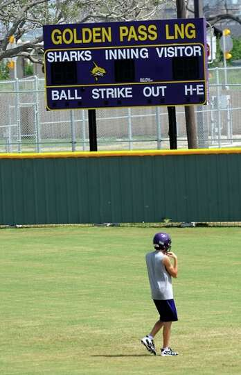 A Sabine Pass football player walks across the baseball field for the first day of two a day practic
