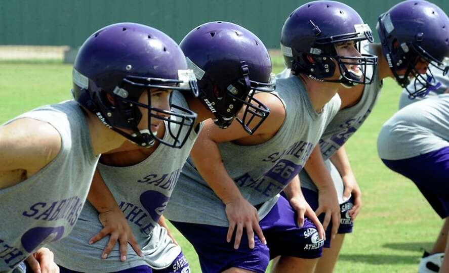 Football players work on their stance at Sabine Pass High School during the first day of two a day p