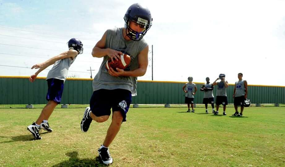 Football players run drills at Sabine Pass High School during the first day of two a day practices i