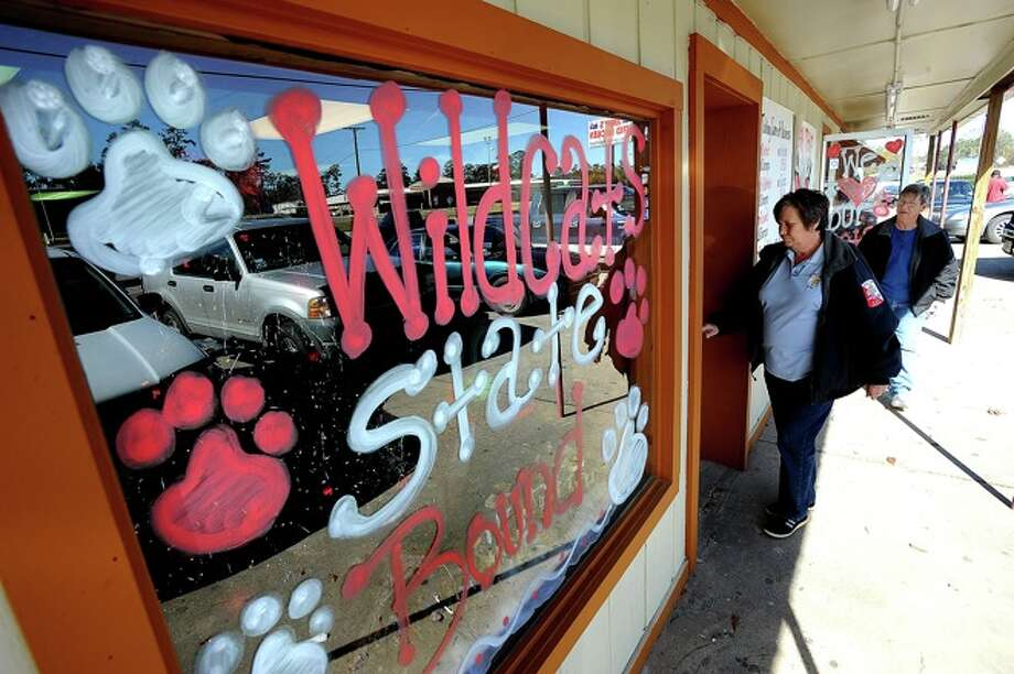Artie Day, left, and Jacque Stephenson enter Jenny's Chicken in Kirbyville. Support for the Wildcats upcoming State 2A Division I football championship runs rampant across the small town. Photo: GUISEPPE BARRANCO