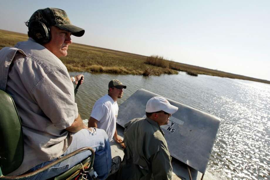 Mark Porter, left, guides his airboat through a marsh while hunting alligators with Roger