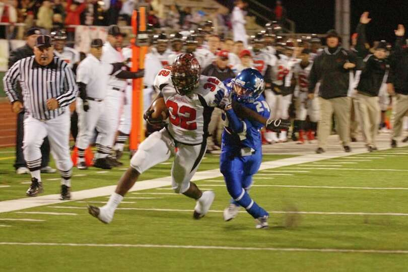 Wildcats running back, Broderick Jackson, drags, Raiders defender, Kevin Ellis, into the end zone fo
