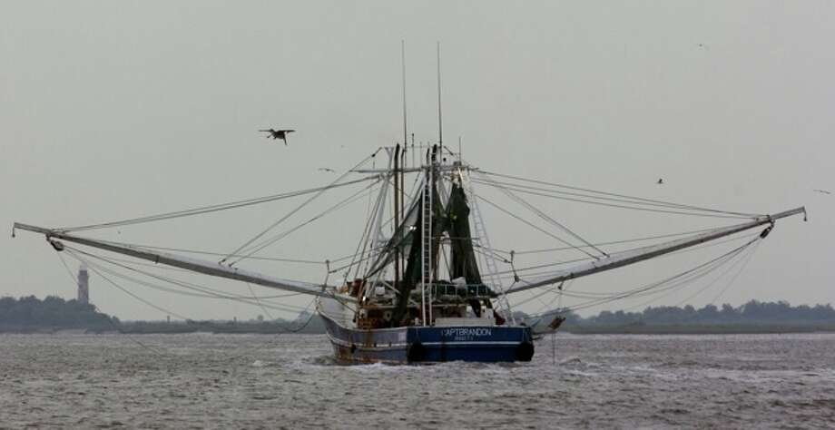 A shrimp boat returns from the Gulf of Mexico through the Sabine-Neches Waterway near the  Sabine Pass lighthouse in May, 2007.  Enterprise file photo Photo: THE ENTERPRISE / The Beaumont Enterprise