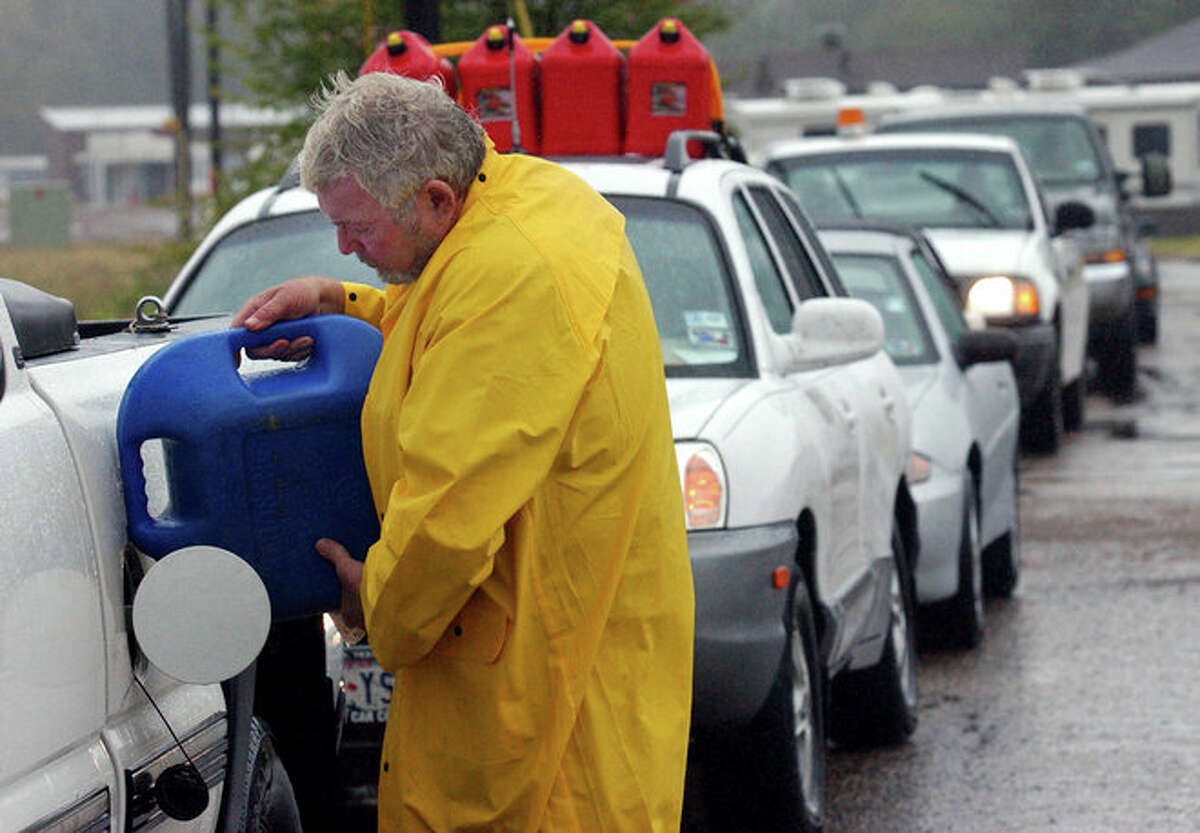 Pat Lemberger poured fuel into his truck while waiting in a line of more than 20 cars to purchase more gas at a Nacogdoches gas station. Hurricane Rita evacuees depleted available gas in the area as they attempted to drive away from the storm's path and toward safe ground.