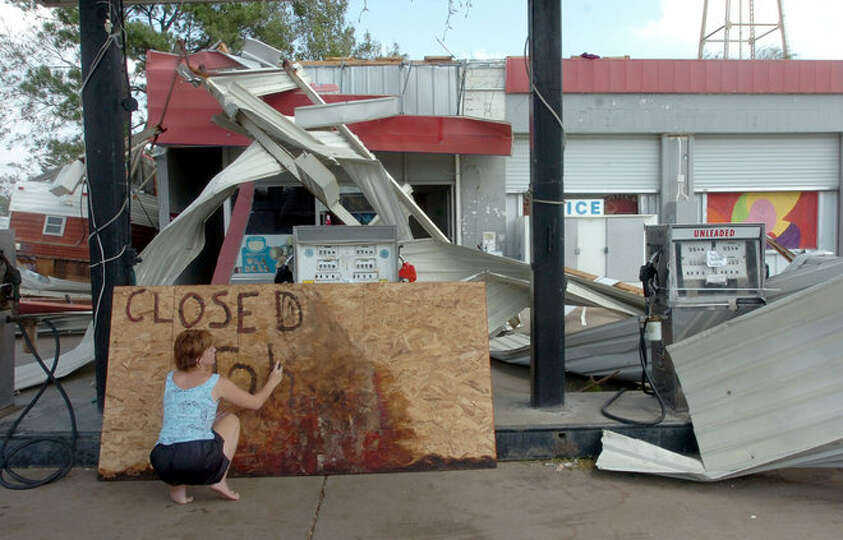 Kasey Simmons paints 'Closed-Johnny is OK' on plywood at the Stop 'N Stay convenience store in Kirby