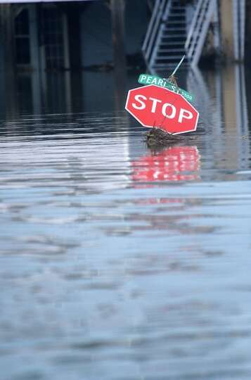 A  Stop  sign is   submerged in flood   waters in  Sabine Pass, Sunday. Tammy McKinley/