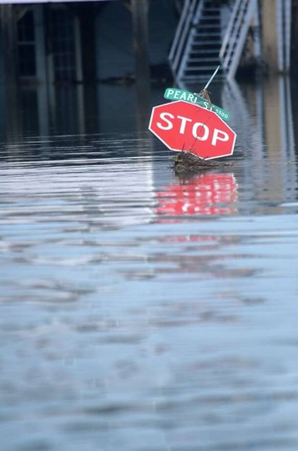 A  Stop  sign is   submerged in flood   waters in  Sabine Pass, Sunday. Tammy McKinley/ Photo: THE ENTERPRISE