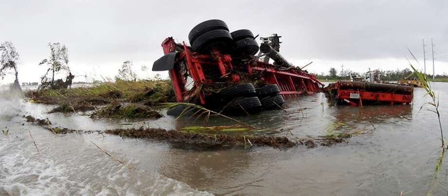 An overturned truck lies  in flood   waters near Highway 87 in  Sabine Pass, Sunday. Tammy McKinley/ Photo: THE ENTERPRISE