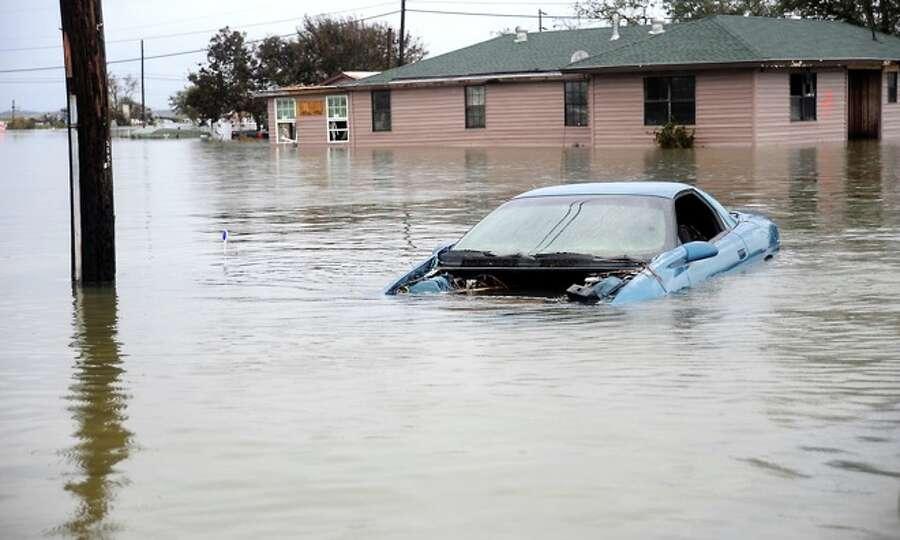 A  vehicle is submerged in flood  waters in  Sabine Pass,  Sunday. Tammy McKinley/