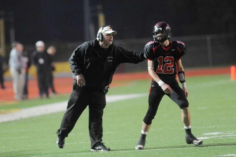 Kirbyville head coach Jack Alvarez, left, sends in play instructions with quarterback Kael Jones dur