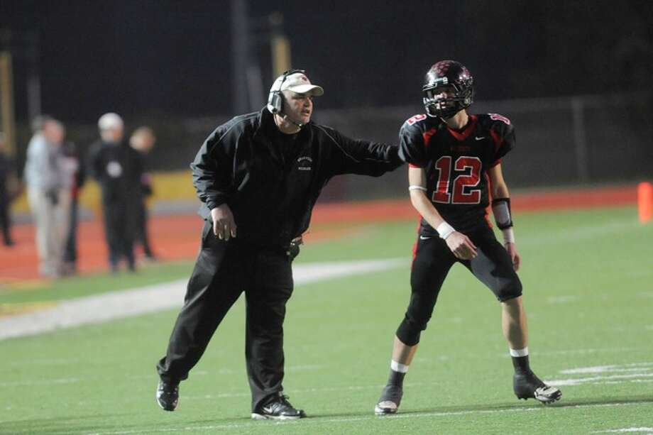 Kirbyville head coach Jack Alvarez, left, sends in play instructions with quarterback Kael Jones during the second half against Pilot Point in the Class 2A Division I title game at Texas State University in San Marcos. Saturday, December 12, 2009. Photo: VALENTINO MAURICIO