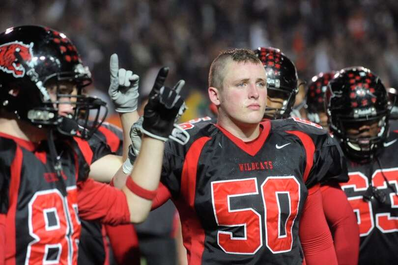 Kirbyville's Dustin West, center, stands with his team for their school song after the Wildcats 35-1