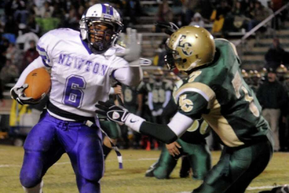 Newton's La RAy Alfred carries the ball as East Chambers' Jacoby Carrington tries to stop him at LC-M in Mauriceville, Friday. Tammy McKinley, The Enterprise Photo: Seames O'Grady