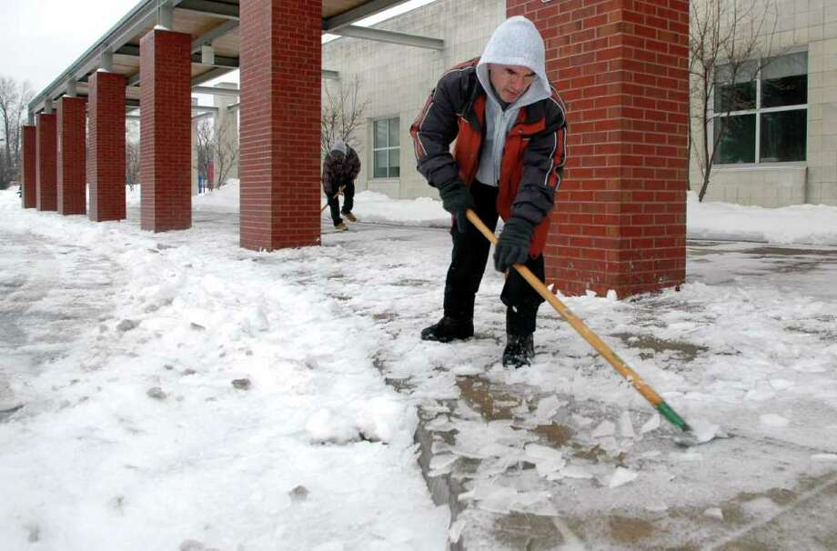 Max Moura, foreground, and Mark Volza clear the sidewalk at McKinley School in Fairfield, Conn as the rain turned to ice on Tuesday, Jan. 18, 2011. Photo: Cathy Zuraw / Connecticut Post