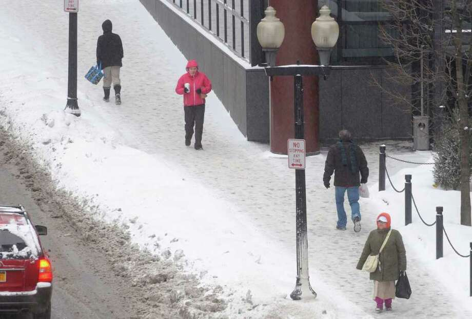 Bundled up against the cold, pedestrians Tuesday make their way along the snow-covered sidewalks on South Pearl Street in downtown Albany.  (Paul Buckowski / Times Union) Photo: Paul Buckowski / 10011776A