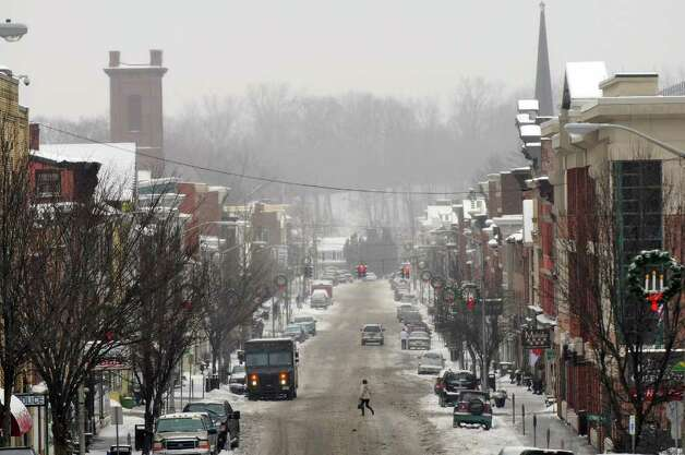 A pedestrian Tuesday crosses a slushy Main Street in Catskill. ( Philip Kamrass / Times Union ) Photo: Philip Kamrass