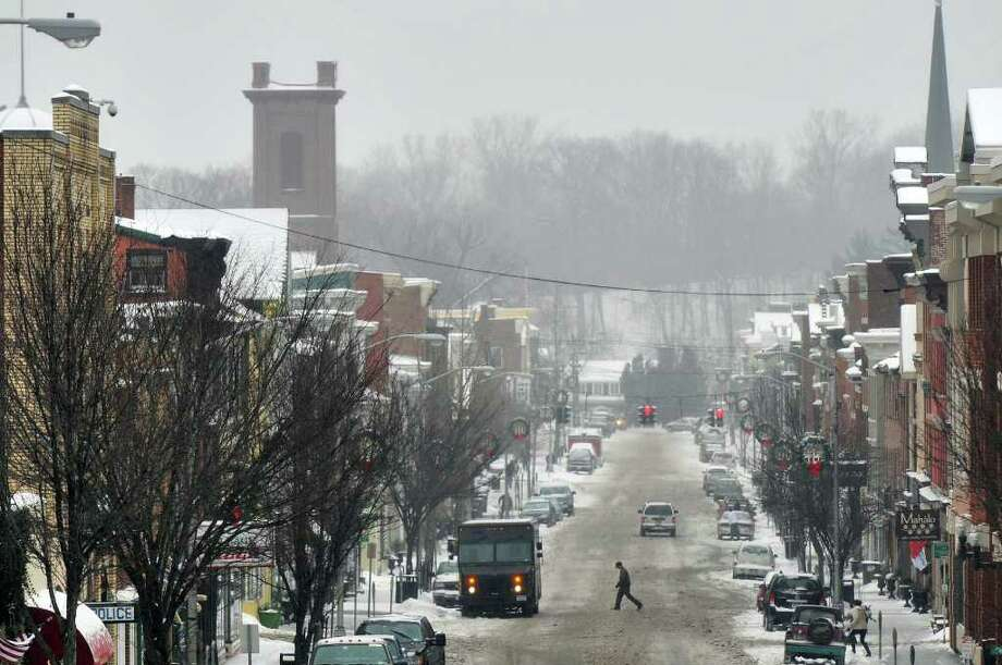 A pedestrian Tuesday crosses a slushy Main Street in Catskill. ( Philip Kamrass / Times Union ) Photo: Philip Kamrass