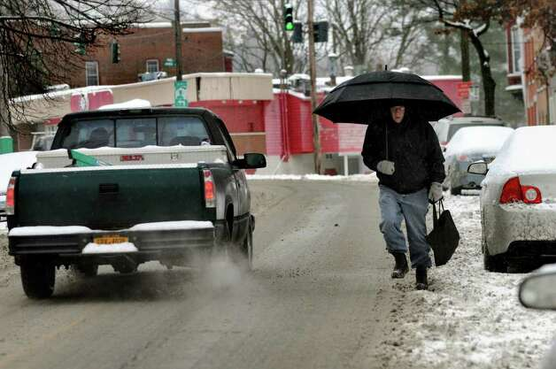 Michael Madsen of Troy navigates the slush and the traffic Tuesday as he walks to work. (Cindy Schultz / Times Union) Photo: Cindy Schultz