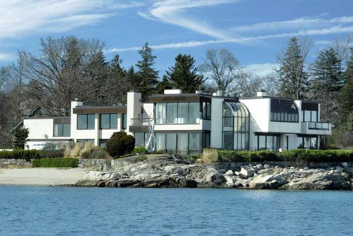 A dramatic waterfront contemporary of more than 10,000 square-foot hosts seven bedrooms, eight baths, elevator, oversized pool and spa and private sandy beach. Lavished with Italian marble and all the amenities of the moment, the house, with spectacular water views across to the islands of Greenwich Harbor, is the creation of billionaire, Leandro Rizzuto, owner of Conair and Cusinart.