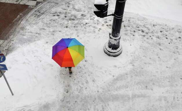 A woman with an umbrella adds a splash of color along a snow-covered sidewalk in Albany on Tuesday. (Paul Buckowski / Times Union) Photo: Paul Buckowski  / 10011776A