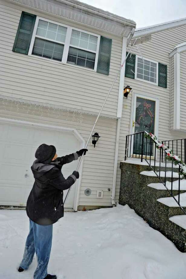 Mary Wolfe, of Colonie, NY uses a snow rake to brake off dangerous icicles from her house on Tuesday.  (Lori Van Buren / Times Union) Photo: Lori Van Buren
