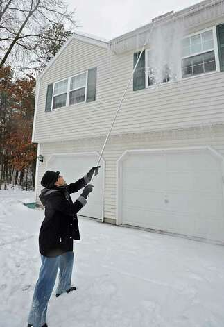 Mary Wolfe, of Colonie, NY uses a snow rake to brake off dangerous icicles on Tuesday.  (Lori Van Buren / Times Union) Photo: Lori Van Buren