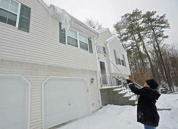 Mary Wolfe, of Colonie, NY uses a snow rake to remove snow from her roof  Tuesday.  (Lori Van Buren / Times Union) Photo: Lori Van Buren