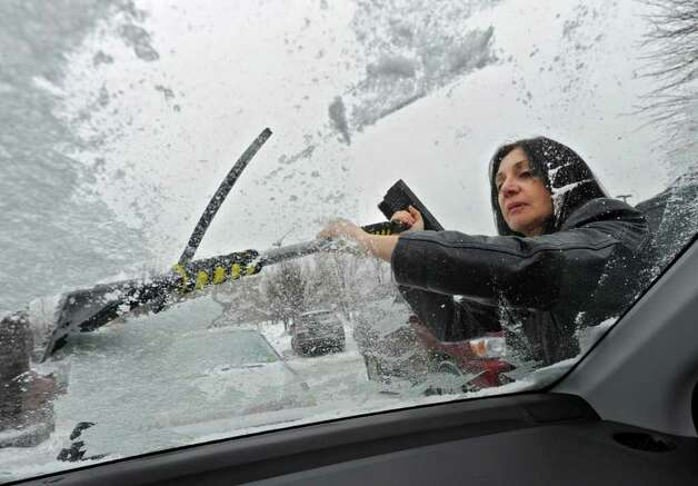 Department of Education employee Jean Holland, of Guilderland, scrapes the ice from her windshield in Colonie Tuesday.  (Lori Van Buren / Times Union) Photo: Lori Van Buren