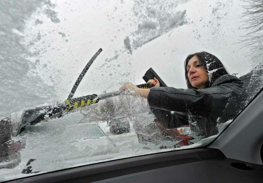 Department of Education employee Jean Holland, of Guilderland, scrapes the ice from her windshield in Colonie Tuesday.  (Lori Van Buren / Times Union) Photo: Lori Van Buren