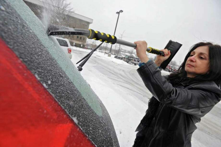 Department of Education employee Jean Holland, of Guilderland, scrapes the ice from her back window of her car in Colonie Tuesday.  (Lori Van Buren / Times Union) Photo: Lori Van Buren