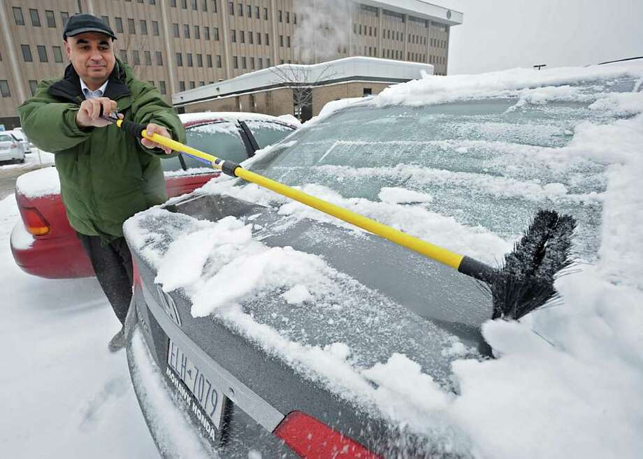 Department of Transportation employee Larry Scotto, of Clifton Park, clears snow and ice from his car in Colonie.  (Lori Van Buren / Times Union) Photo: Lori Van Buren