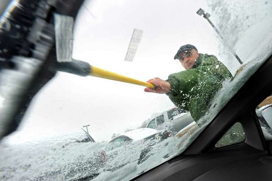 Department of Transportation employee Larry Scotto, of Clifton Park, clears off ice and snow from hi