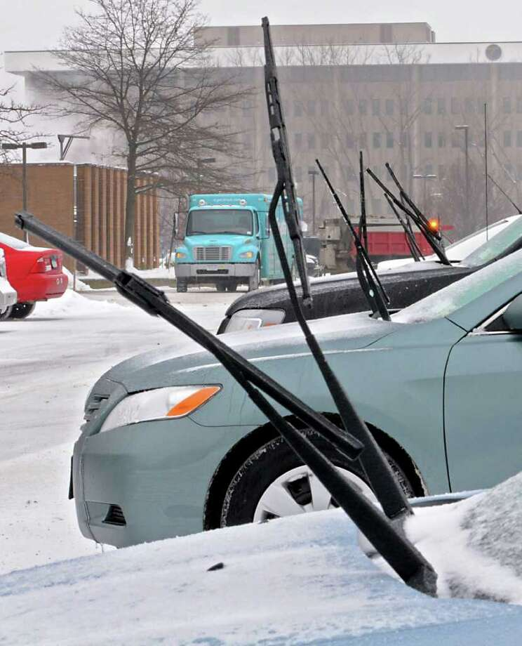 A row of cars have their windshield wipers up for easier cleaning behind a state office building in Colonie on Tuesday. Lori Van Buren / Times Union) Photo: Lori Van Buren