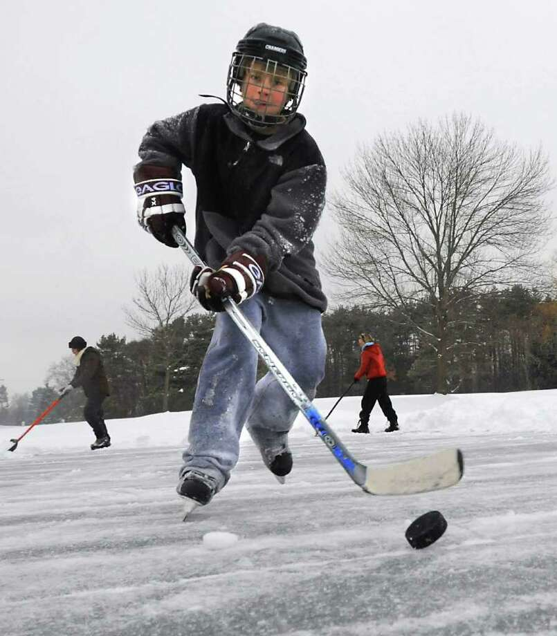 Trevor Long, 10, of Guilderland, doesn't let a little freezing ruin his school snow day by playing hockey on a  pond at Western Turnpike Golf Course in Guilderland Tuesday. His mom Sherri Long and Ellen Roy, left,  help to shovel the snow off the ice.  (Lori Van Buren / Times Union) Photo: Lori Van Buren