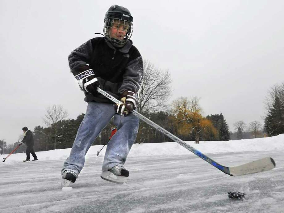 Trevor Long, 10, of Guilderland, doesn't let a little freezing ruin his school snow day by playing hockey on a pond at Western Turnpike Golf Course in Guilderland.  His mom Sherri Long and Ellen Roy, left,  help to shovel the snow off the ice.  (Lori Van Buren / Times Union) Photo: Lori Van Buren