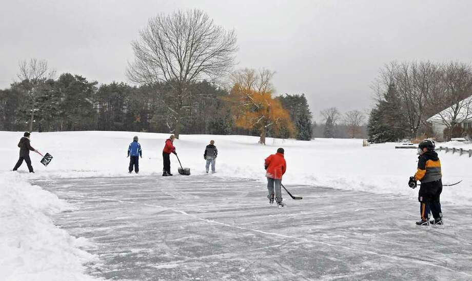 Some Guilderland boys, with help from moms shoveling, don't let a little freezing rain their school snow day by playing hockey on an ice skating pond at Western Turnpike Golf Course in Guilderland. From left, Ellen Roy, Chris Roy, Sherri Long, Trevor Long, Michael Carlow, and Sam Groezinger make most of a messy day.  (Lori Van Buren / Times Union) Photo: Lori Van Buren