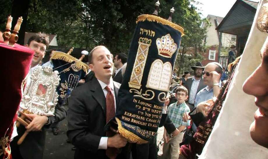 Brian Roitman, of Stamford, carries the synagogue's newest Sefer Torah during the holy book's dedication at Young Israel of Stamford on Sunday, Sept. 13, 2009. It was dedicated in memory of his 2 1?2 year-old son Kerav who died last August. Photo: Chris Preovolos / Stamford Advocate